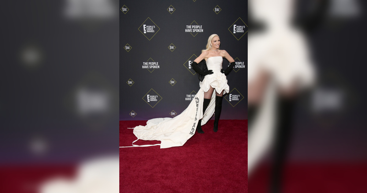 Fotogalería: Gwen Stefani fue el centro de atención gracias a el vestido blanco off shoulders, de falda midi con holanes y una cola larguísima en la que se leyó: Fashion Icon Award. (6/17) (Fuente: E! Entertainment)